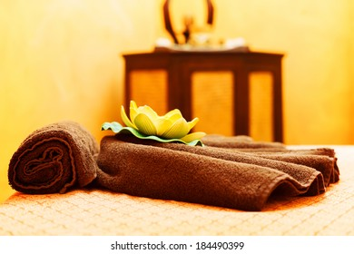 Towels and orchid flower decorating a massage table for thai massage