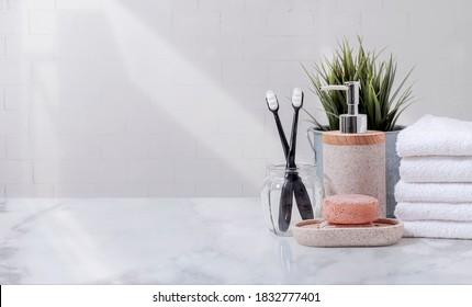 Handtücher, Zahnbursche und Keramik-Shampoo oder Seife auf dem obersten Marmortisch auf Badhintergrund.