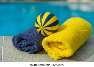 Towels and toys in blue and yellow near the swimming pool
