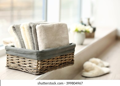 Towels in wicker basket with flowers on windowsill