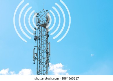 a tower with antennas that broadcasts a signal against a blue sky with clouds