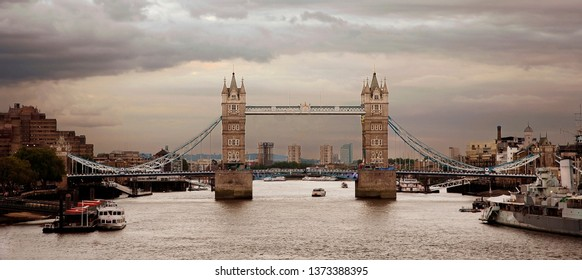 Tower Bridge at dusk over dramatic cloudy sky, pier and tour boat present.