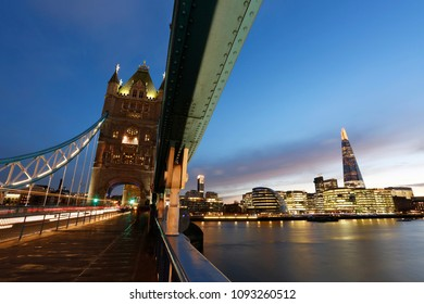 Tower Bridge, in Tower Hamlet, at sunset. Blue sky, River Thames, City Hall and The Shard present. Nobody appeared and traffics moving in motion.