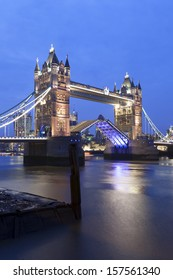 Tower Bridge illuminated at night over the River Thames in London, England.