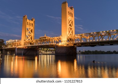 Tower Bridge and lights reflected on the Sacramento River. Sacramento and Yolo Counties, California, USA.