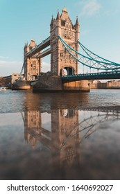 Tower Bridge in London reflected in the marble wall surrounding the boardwalk along the River Thames.