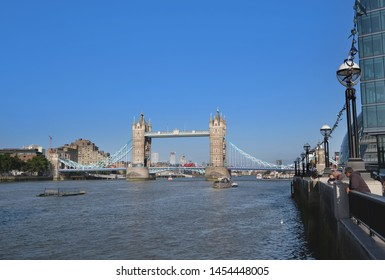 Tower Bridge, London, United Kingdom 6th July 2019: Tower Bridge seen from south bank, tourists enjoying evening sunshine