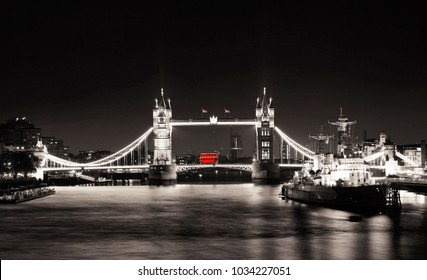 Tower Bridge seen from South Bank at night, Belfast Ship, Routemaster bus and Union Jack present.