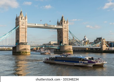 Tower Bridge (Symbol of London City Skyline Landmark) and Thames Clippers cruise under Clear Blue Sky at Sunset in Summer. River Bus Boat Commuter and Tourist service on the River Thames, England, UK