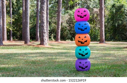 A tower of bright colorful jack o lantern halloween candy buckets
