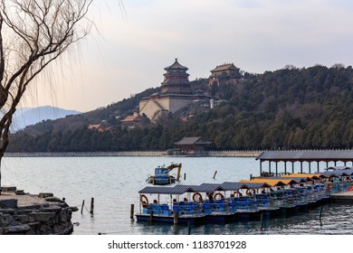 Tower of Buddhist Fragrances and other temples seen past boats from across the lake at the Summer Palace, Beijing, China.