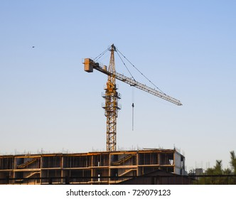 Tower building crane near the new house under construction