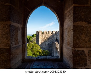 Tower of the castle of Sao Jorge Castle seen through an ancient arch windows, a Moorish castle which sits on hilltop and overlooking the historic center of Lisbon and and Tagus River