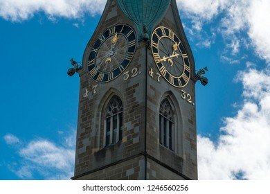 Tower of Fraumünster Cathedral with two huge clock-faces, hands showing twenty minutes to one o'clock. Blue sky and white clouds as framing