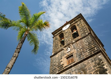 The tower of the church Iglesia Matriz de El Salvador with a palm tree and blue sky in Santa Cruz de La Palma, Spain.