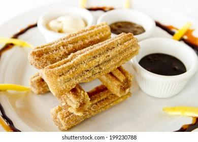 A tower of churros with sauces.