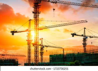 Tower crane and building construction site silhouette at sunrise.