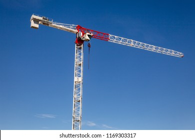 Tower crane at a construction site against the blue sky - under construstion concept