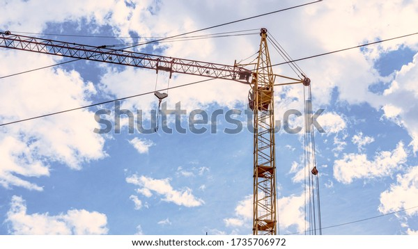 Tower crane at major construction site. The construction crew uses the tower crane to lift building materials. Bottom view of construction crane, white clouds in the background.