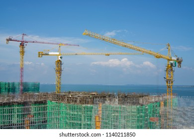 Tower crane on top of a large building in construction work, there're builder working on top floor, scaffolding on each story and cover by green net protection, sea on baclground under clear blue sky