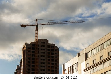 tower crane stands in the background of a new unfinished skyscraper, evening sky with clouds, bottom view. city economy development concept