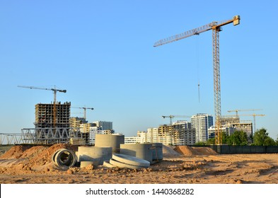 Tower cranes constructing a new building at a construction site. Renovation program, concept of the building industry. Installation of water main, sanitary sewer, storm drain systems in city - Image