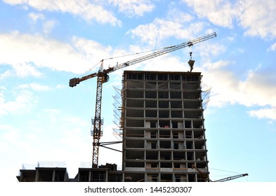 Tower cranes and new residential high-rise buildings at a huge construction site on background blue sky background. Building construction, installation of formwork and concrete structures - Image