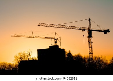 Tower cranes on a construction site behind buildings and trees, with a colorful sunset in Freiburg, Germany