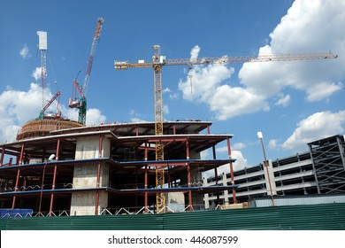 Tower cranes on industrial building construction over blue sky with light clouds horizontal view