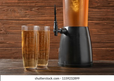 Tower dispenser and glasses with cold beer on table