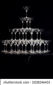 tower of empty champagne glasses on a black background