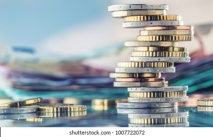 Tower with euro coins and banknotes in the background.