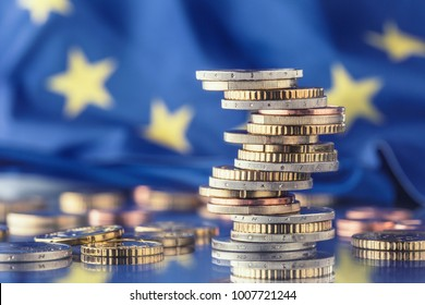 Tower with euro coins and flag of European Union in the background.