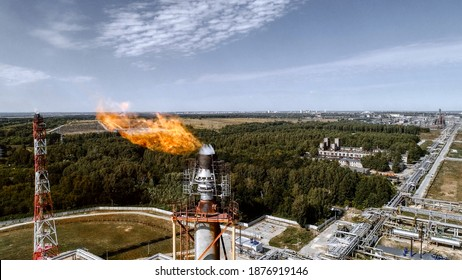 A tower for flaring associated gas at a petrochemical plant. Fiery torch. Aerial view
