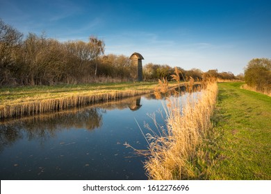 The Tower hide on the banks of Burwell Lode waterway on Wicken Fen nature reserve in warm evening sun, Cambridgeshire; England; UK - Shutterstock ID 1612276696