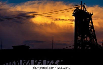 A tower of a lift bridge in Cleveland Ohio silhouetted against orange clouds at sunset