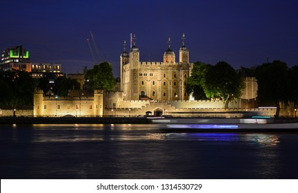 The Tower of London, an old castle and a museum where crown jewels are stored, seen from the River Thames at night. The famous fortress is located on the Tower Hill in the center of London, England