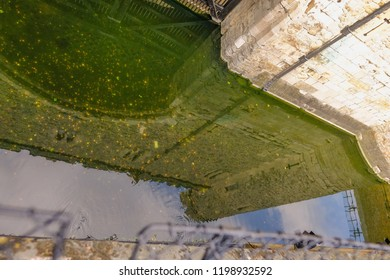 Tower of London, London, UK- June 8, 2018:  Tower of London reflection in the water at Traitor's Gate.  Shows the coins thrown in for good luck.