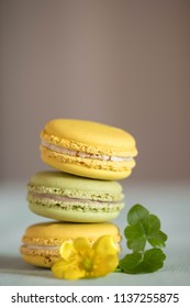 Tower from macarons on blue wooden table with nice yellow flower