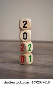Turm aus Würfeln und Würfeln mit den Jahren 2020 und 2021 auf Holzhintergrund
