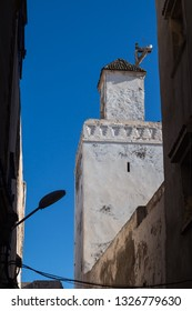 Tower of a mosque with old white facade. Buildings of the hosues around. Silhouette of a street lamp. Bright blue sky. Essaouira, Morocco.