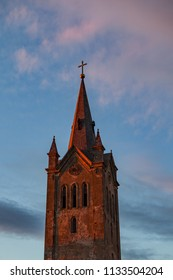 Tower of the old church lit by sunset light with dramatic clouds. Cesis, Latvia.