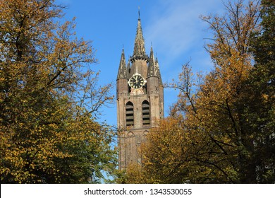 Tower of the Old Church (Oude Kerk) of Delft, Holland with trees in autumn