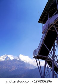 a tower on poonhill with the himalayan mountains in background.