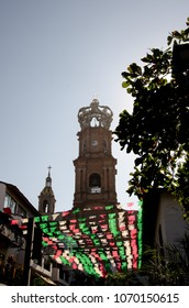"Tower of Our Lady of Guadalupe in distance with sun-lit ""Dia de los Muertos"" flags and a tree silhouette in foreground in Puerto Vallarta, Mexico."
