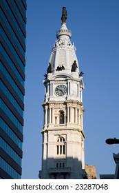 Tower of the Philadelphia (Pennsylvania, USA) city hall next to modern office building.
