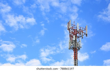 Tower poles and wireless telephone antennas against blue sky background.