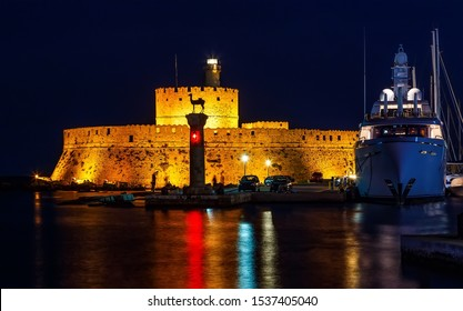 Tower of St. Nicholas in Rhodes Greece by night - Bluelight. Motion blur on greek flag and sail masts. Original colors.