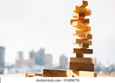 The tower stack from wooden blocks toy with city and sky background. Learning and development concept.