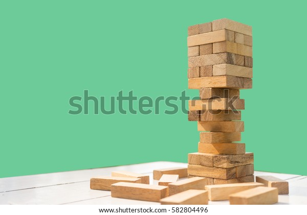 The tower stack from wooden blocks toy with greenery background. Learning and development concept.